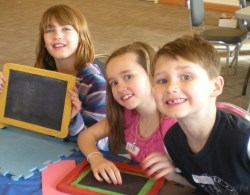 3 kids smiling with slate boards