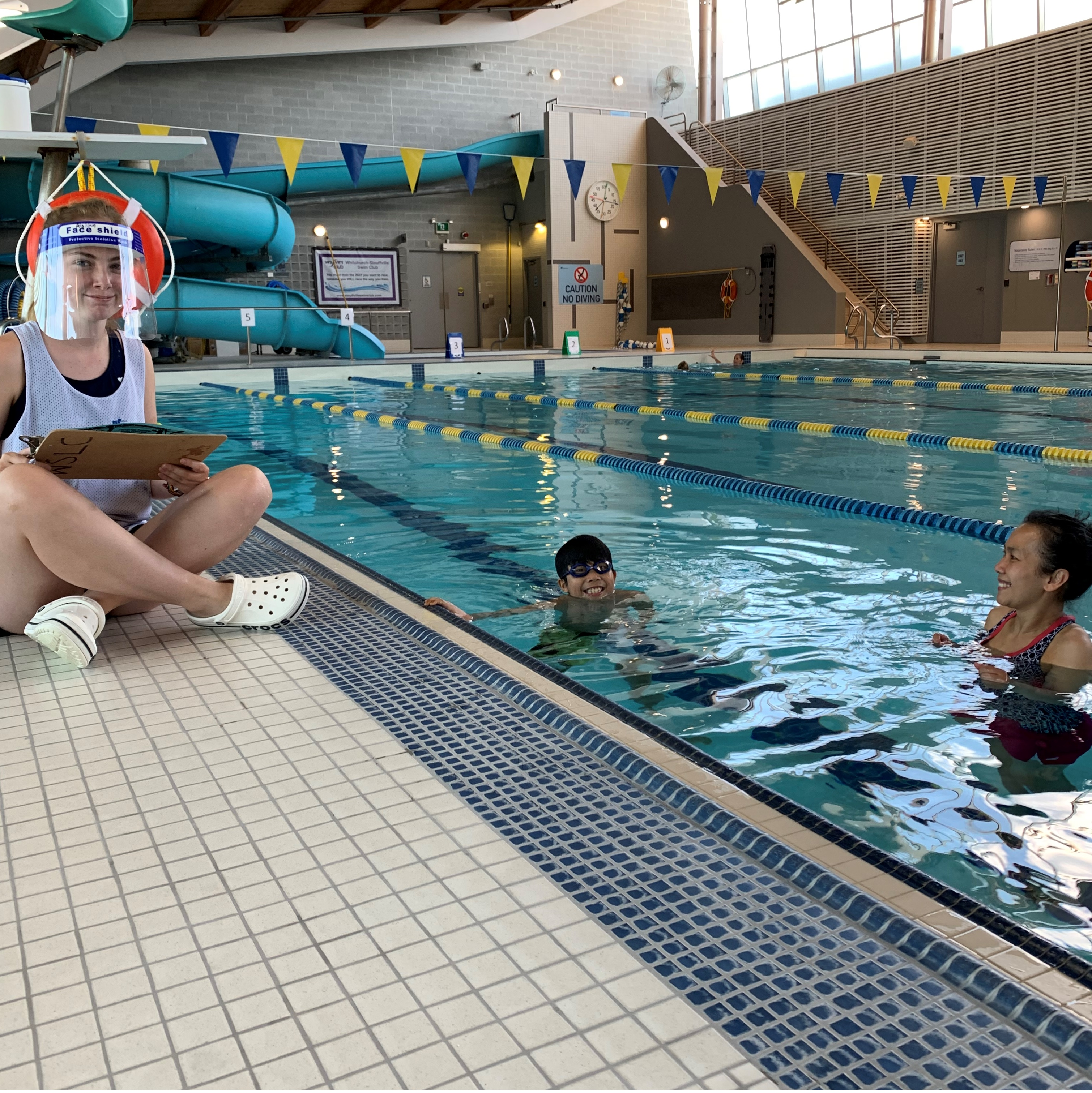 Instructor teaching from the deck and Parent in the water for Support